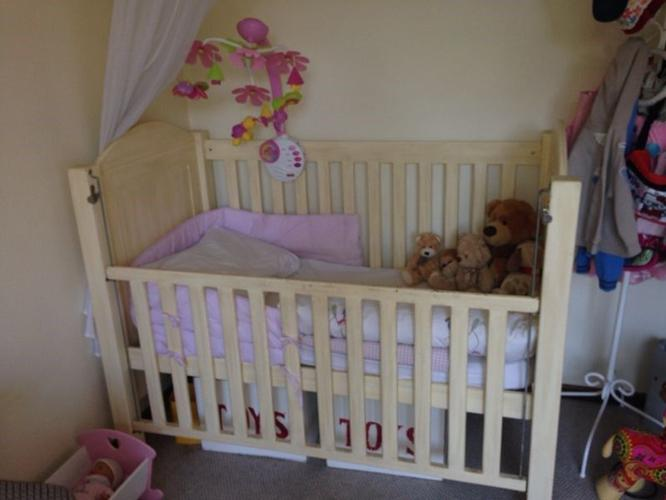 Cream baby cot with drop down side