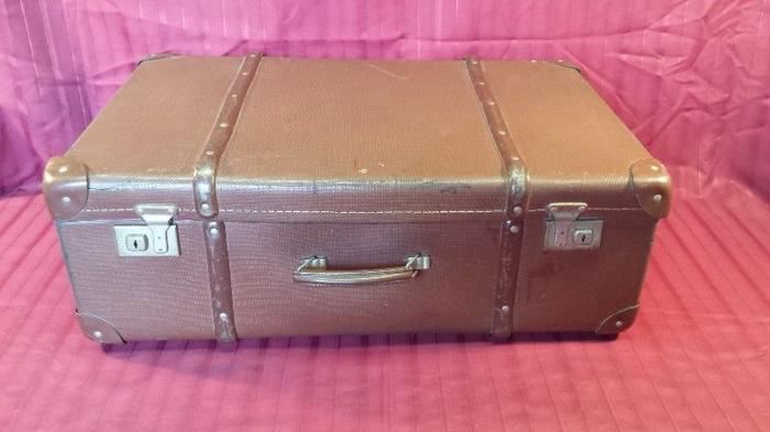 Large, old brown travelling suitcase.