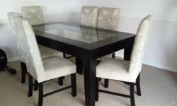 An elegant dark wood and glass dining room table with 6