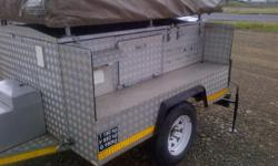 Camping trailer with roof top tent. Tent goes right