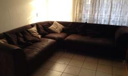 Dark brown corner couches with pillows in good