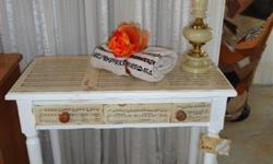An oak table been decoupaged with sheet music. Has