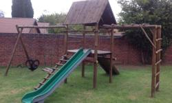 Wooden jungle gym, consists of 2 swings, slide,monkey
