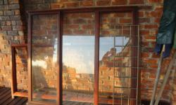 Meranti glazed window with burglar bars. In excellent
