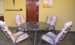 Table with glass top and 4 chairs with cushions