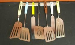 Rack of old kitchen utensils. Spatulas' of all sizes