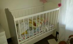 Wooden cot with extra draw and adjustable side.